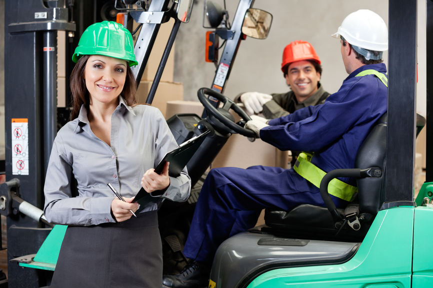 Confident Female Supervisor With Forklift Driver At Warehouse